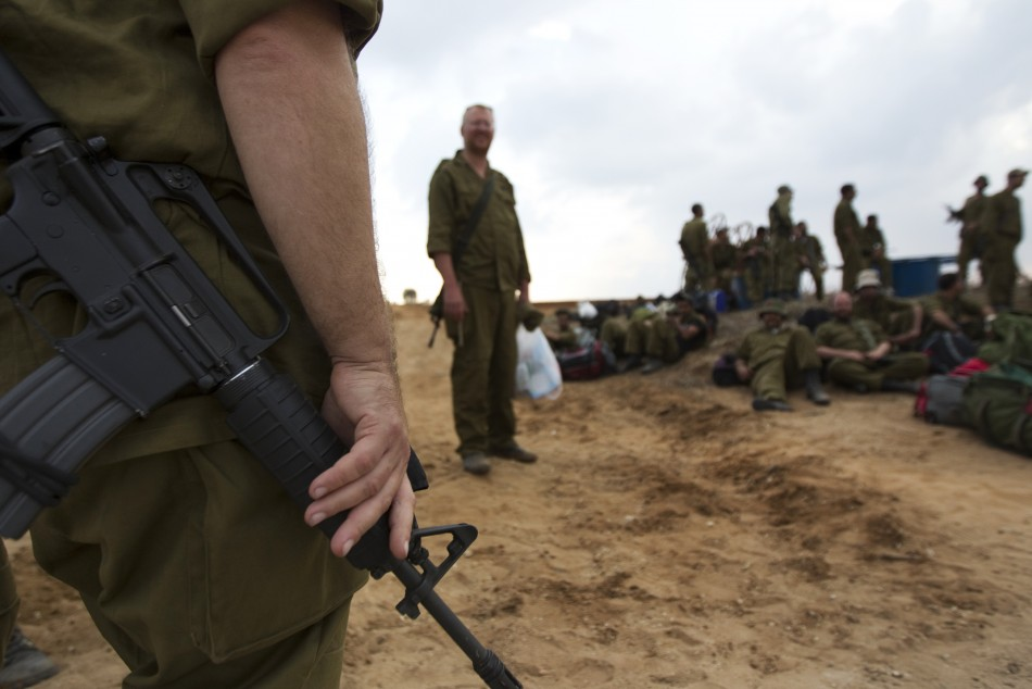 An Israeli reservist soldier holds his weapon as others wait with their gear before going home,