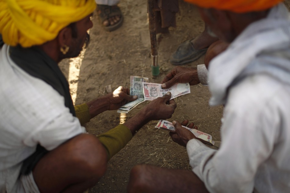 Camel herders count money at Pushkar Fair in the desert Indian state of Rajasthan