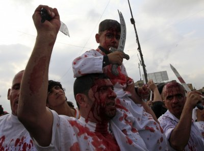 Shiite Muslim worshippers, stained by their own blood from self inflicted wounds