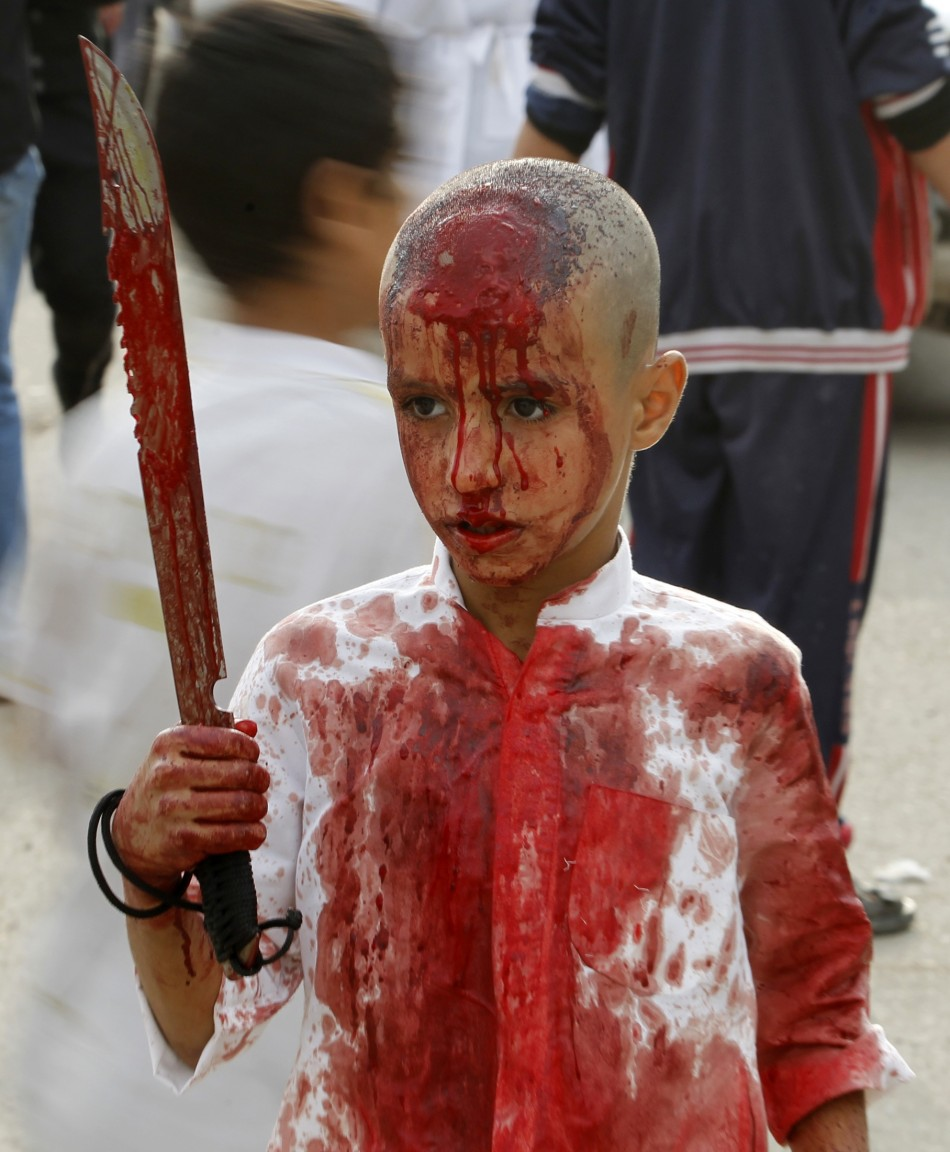 An Iraqi Shiite Muslim child gashes his forehead with a sword