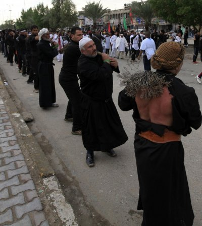 Shiite pilgrims beat themselves with iron chains as they take part in the Ashura procession in Baghdad