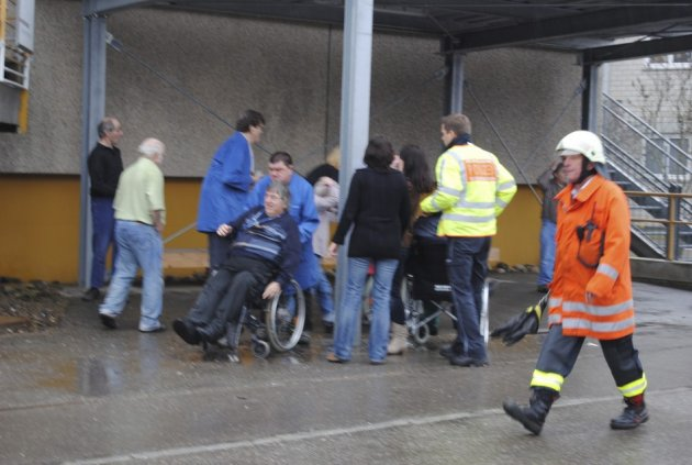 People are evacuated from the scene of a fire in a workshop for disabled people in Titisee-Neustadt