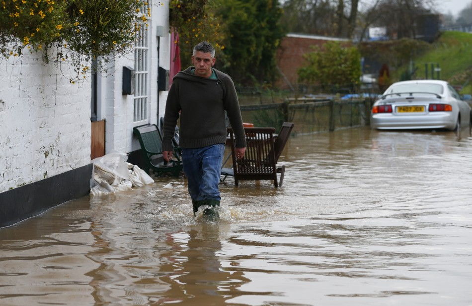 A man walks through floodwater  in Tewkesbury, south western England (Reuters)