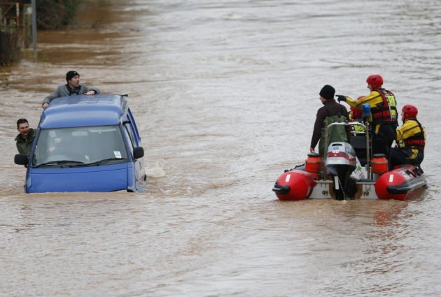 Firemen in a rescue dingy pass a van driving along a flooded street on the outskirts of Gloucester (Reuters)