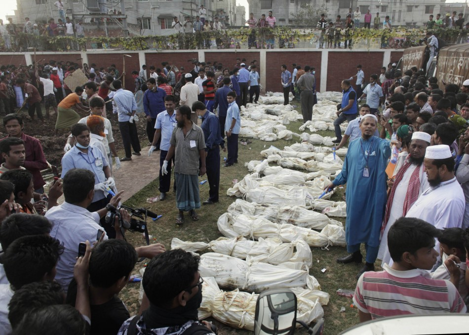 Bodies of unidentified garment workers, who died in fire in a garment factory, are lined up before a mass burial at a graveyard in Dhaka