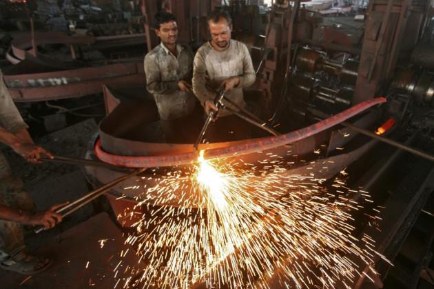 Labourers work inside an iron factory