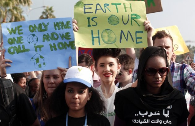 Activists march to demand action to address climate change in Doha