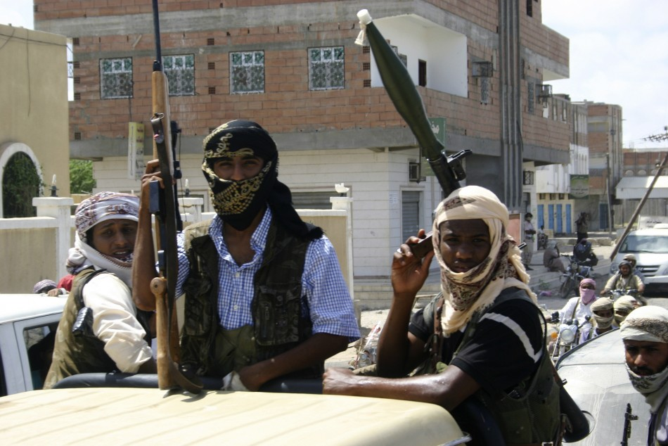 Members of Ansar al-Sharia, an al Qaeda-affiliated group, carry their weapons as they ride on a truck in Jaar
