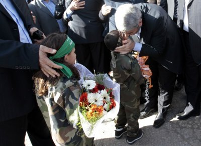 Hamas chief Khaled Meshaal kisses a Palestinian boy upon his arrival at the Rafah crossing in the southern Gaza Strip