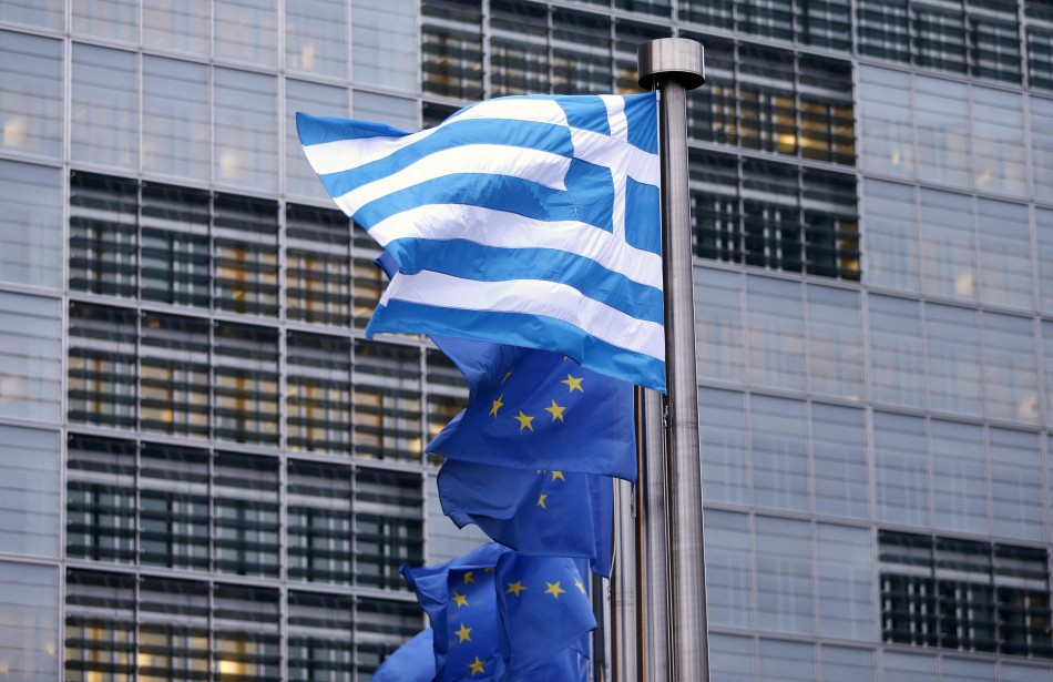 A Greek national flag flies next to EU flags