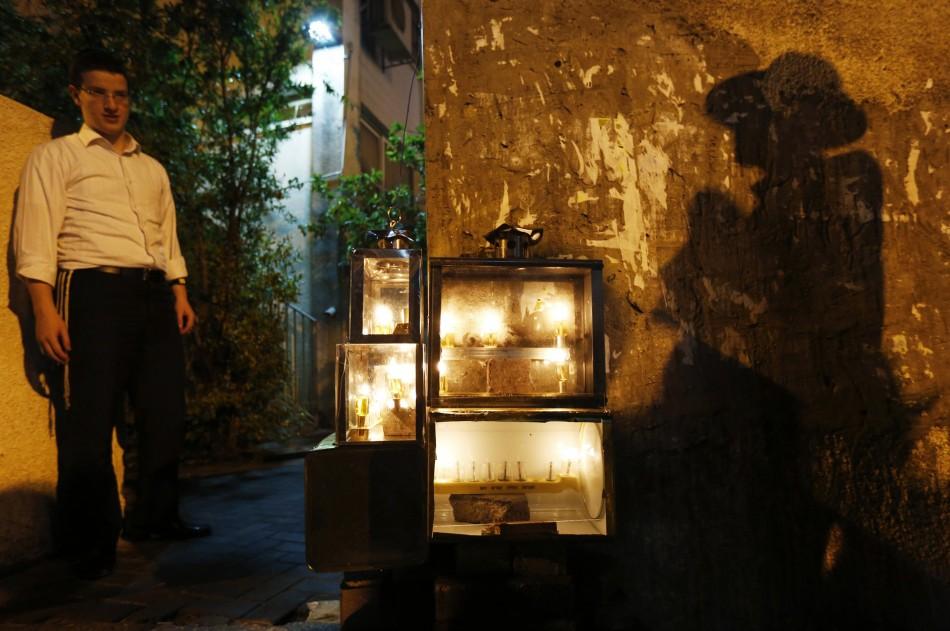 An ultra-Orthodox Jewish man casts a shadow near candles lit for Hanukkah in Ashdod