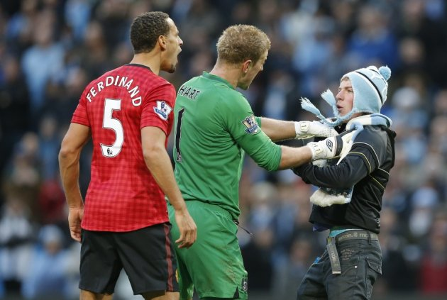 Manchester City's Joe Hart prevents a supporter from reaching Manchester United's Rio Ferdinand after being struck by an object thrown from the crowd (Reuters)
