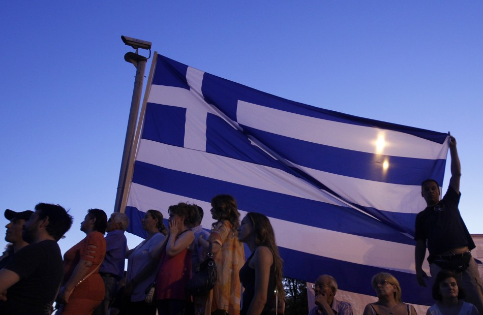 Supporters of the extreme right Golden Dawn party stand below a Greek flag as they attend a pre-election rally in Athens