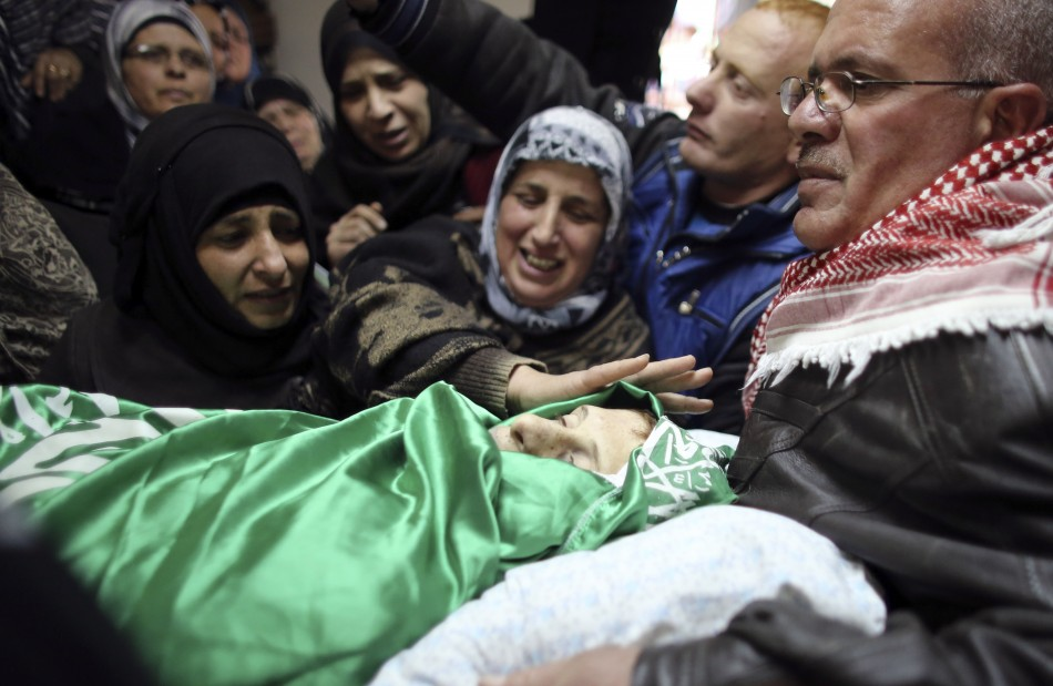 Relatives of Palestinian teenager Salaymeh mourn during his funeral in Hebron