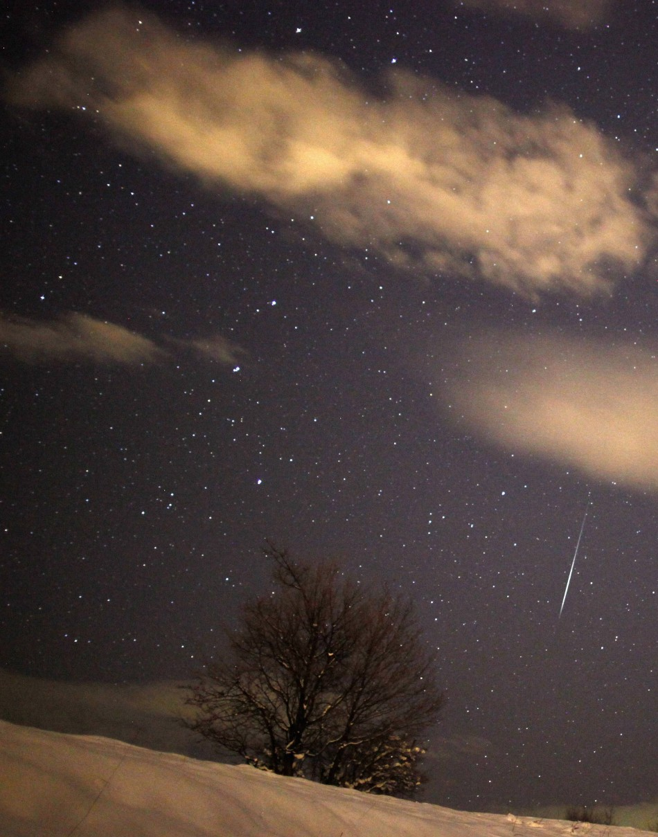 A meteor streaks past stars in the night sky over the village of Pesevici