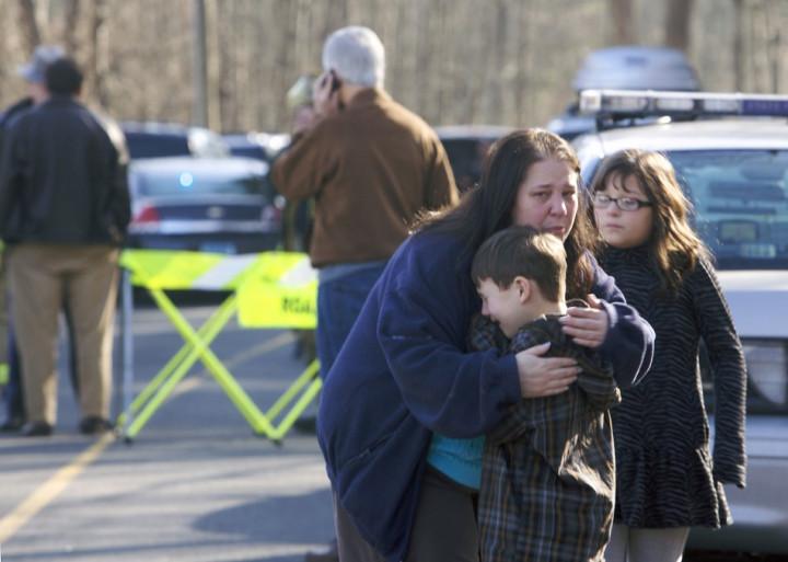 A woman comforts children at scene of massacre