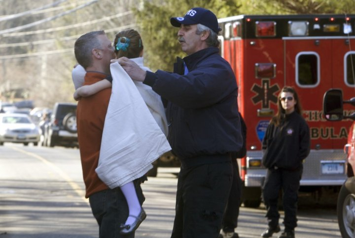 A Sandy Hook pupils is carried to safety after the massacre