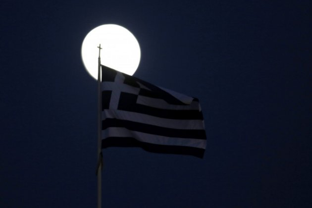 A Greek flag flutters in front of the moon in Athens