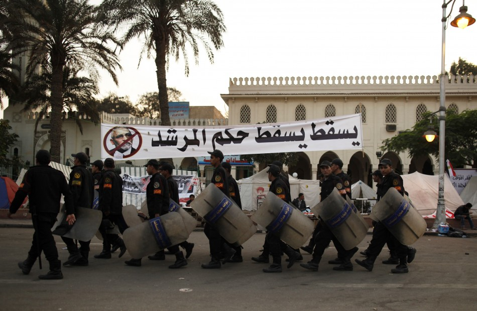 Riot police walk past a banner with a defaced photo of the Muslim Brotherhood's supreme guide, Mohamed Badie, in Cairo