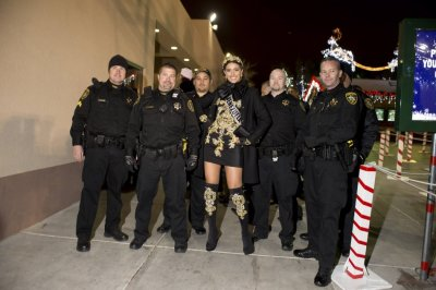 Miss Venezuela Quintero stops for a photo with members of the LVPD during the Miss Universe National Gift Auction in Las Vegas