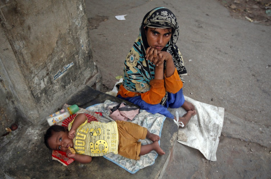 Polio patient Rukhsana, 32, begs with her eight-month old boy Waheed outside a mosque in Karachi