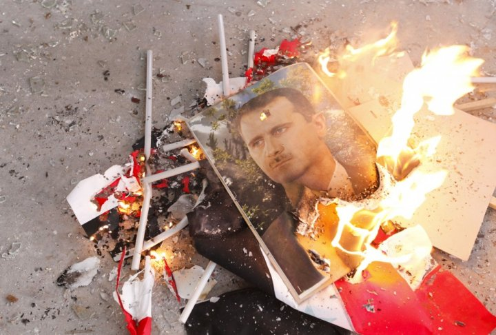 Pictures of Syria's President Bashar al-Assad and Syrian flags burn after being set on fire by Free Syrian Army