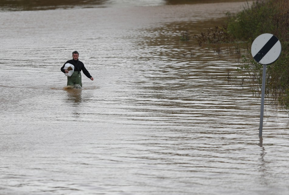 A man wades up a flooded street after rescuing items from his home (Reuters)