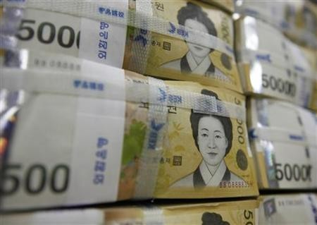 Fifty-thousand-won notes are piled up after being counted at a bank in Seoul