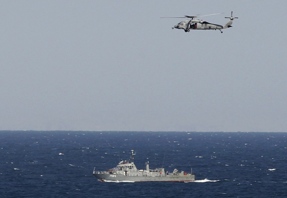 A helicopter from the Nimitz-class aircraft carrier USS Abraham Lincoln hovers over an Iranian patrol ship