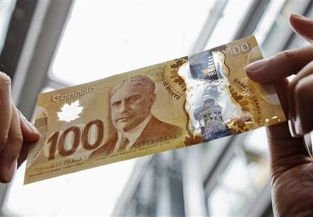 A man holds the new Canadian 100 dollar bill made of polymer in Toronto.