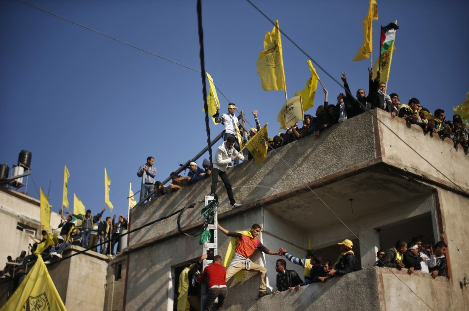 Palestinians stand atop a building as they take part in a rally marking the 48th anniversary of the founding of the Fatah movement, in Gaza City