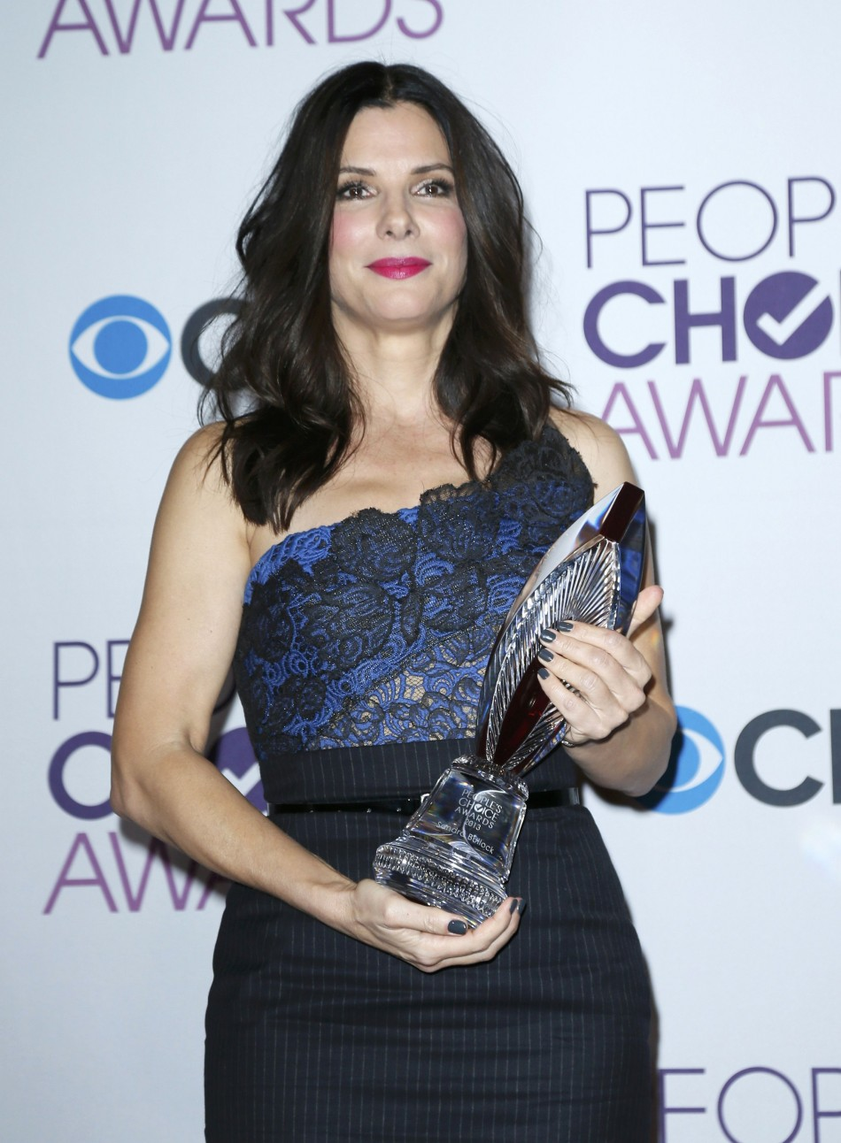 Actress Sandra Bullock poses backstage after being honored with the favorite humanitarian award at the 2013 People's Choice Awards in Los Angeles