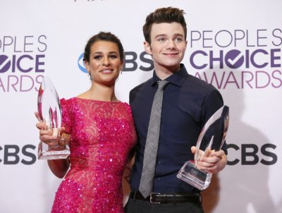 Actors Lea Michele and Chris Colfer hold their awards backstage at the 2013 Peoples Choice Awards in Los Angeles
