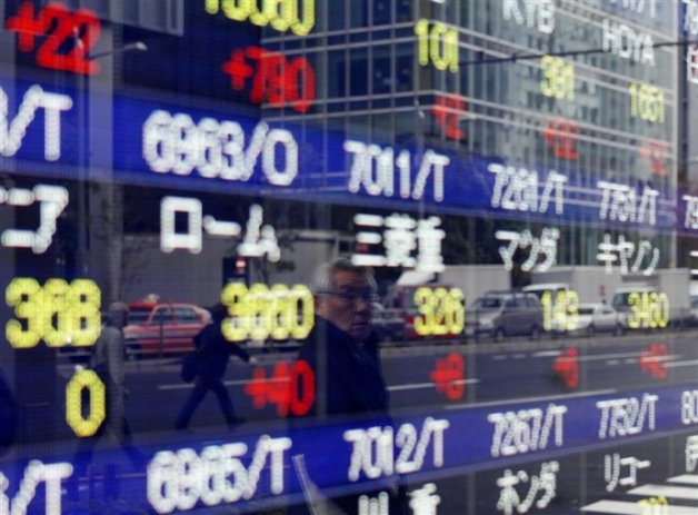 A man is reflected on a stock quotation board showing Japanese companies' stock prices outside a brokerage in Tokyo