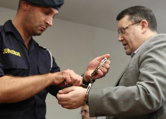 Austrian Gottfried Kuessel has his handcuffs removed in a courtroom in Vienna