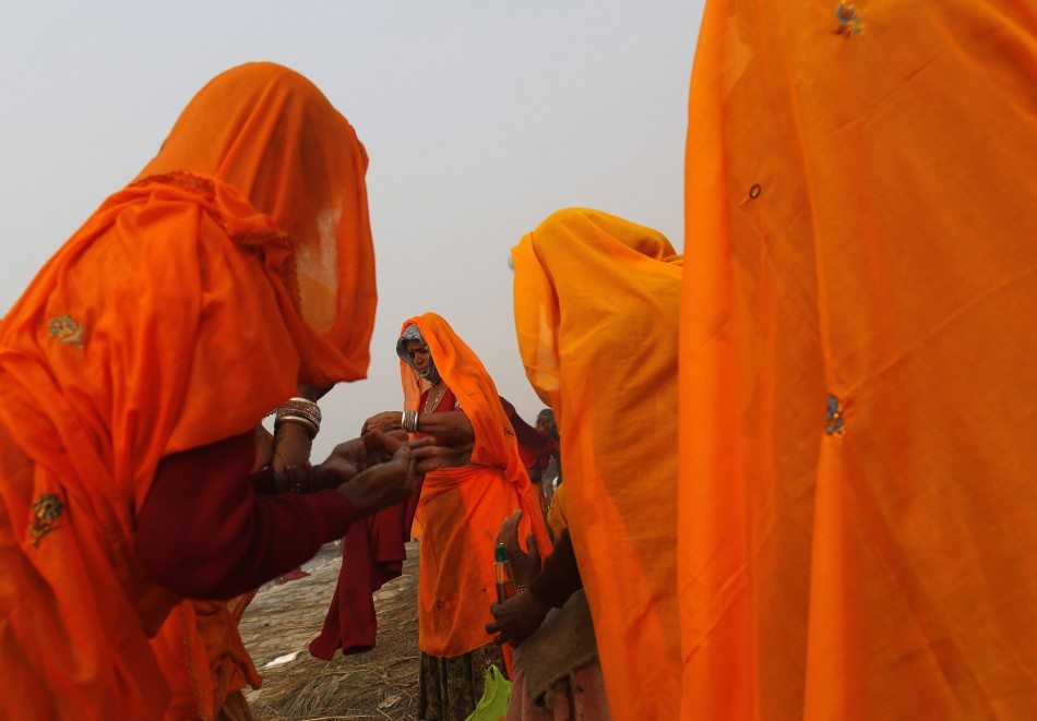 Hindu devotees apply oil on bodies after taking holy dip in river Ganges ahead of Kumbh Mela in Allahabad