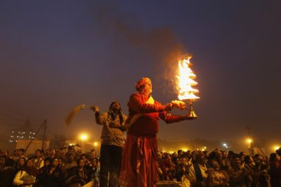 Hindu priest holds oil lamp as performs evening prayers near banks of river Ganges ahead of Kumbh Mela in Allahabad