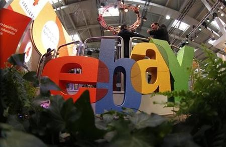 Visitors chat next to Ebay logo at CeBIT computer fair in Hanover