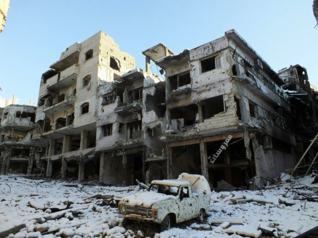 A damaged car and buildings covered with snow at Jouret al Shayah area in Homs