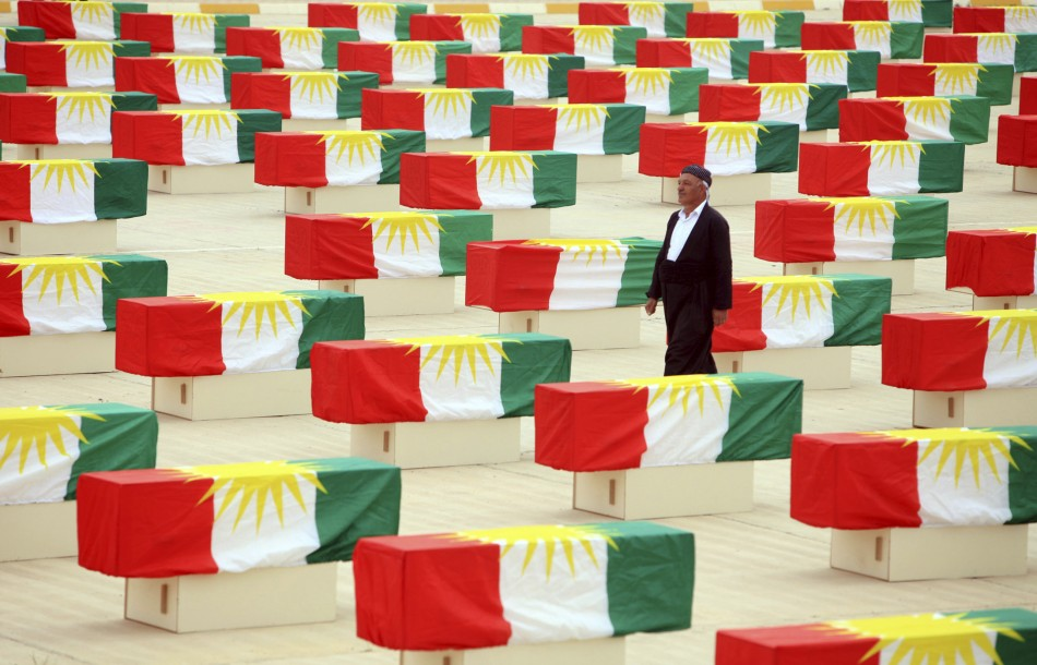 A Kurdish man walks between coffins draped with Kurdish flag containing the remains of victims during a burial ceremony in Sulaimaniya