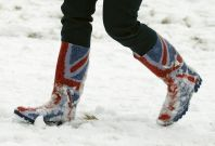 A woman walks through snow in Wellington boots printed with the Union flag in Newtown Linford