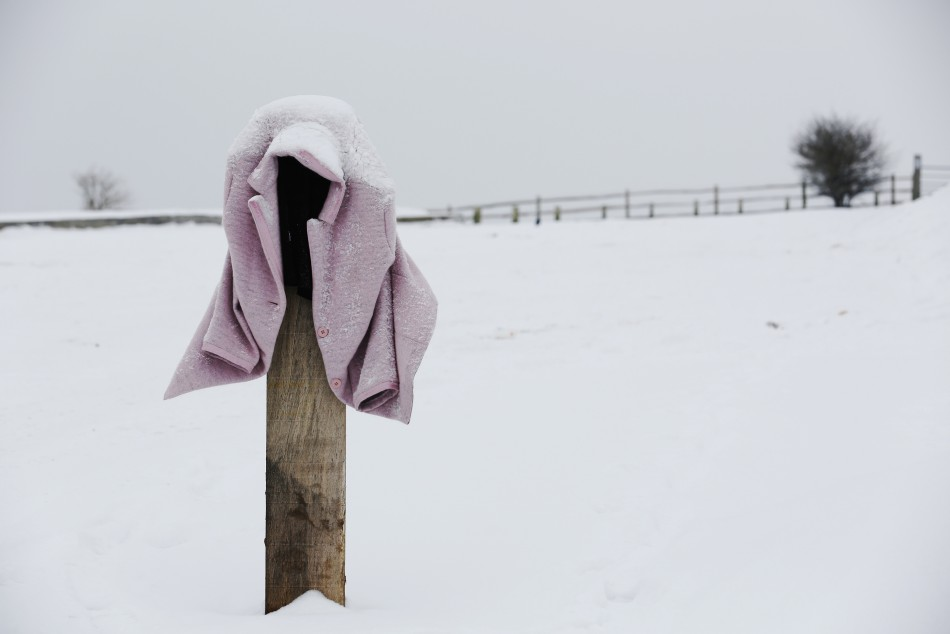 A snow-covered coat is left hanging on a pillar in a car park near Hassocks in south east England
