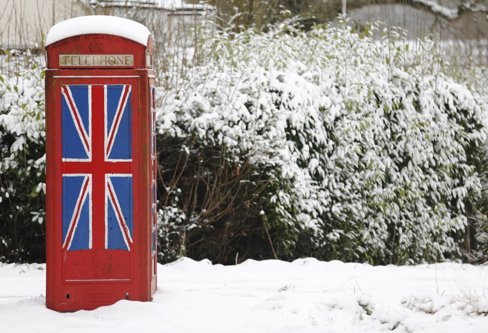 An old telephone box painted with the Union Flag stands out in the snow at Staplefield in south east England
