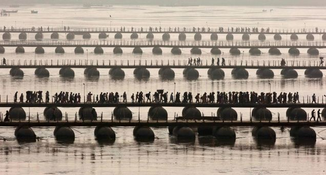 Hindu devotees cross pontoon bridges spanning river Ganges during first