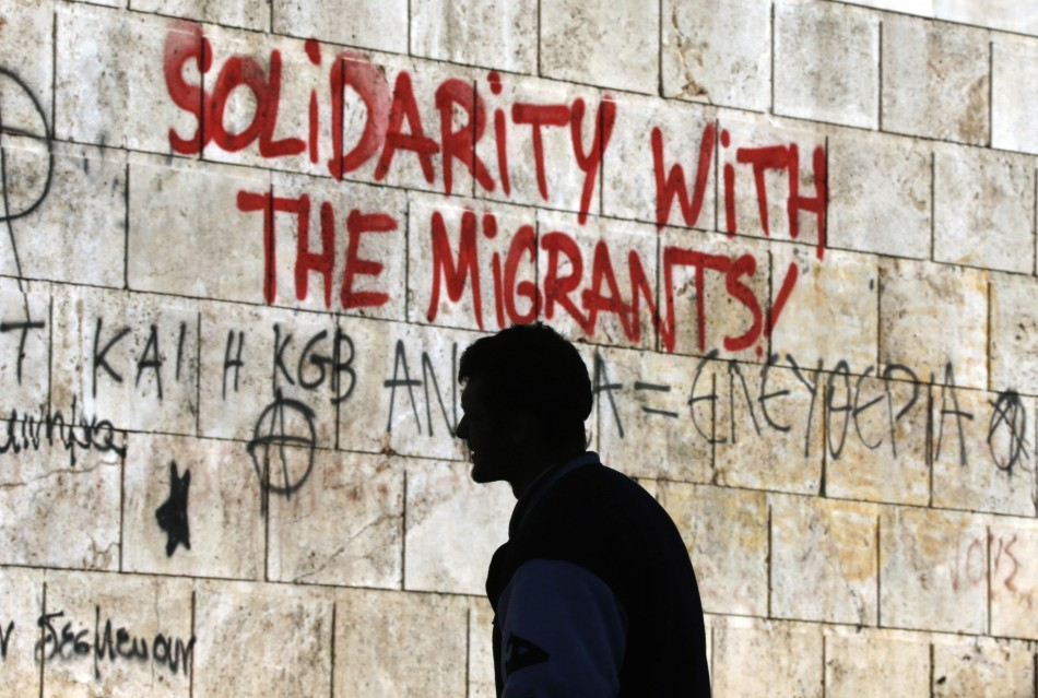 A man walks past graffiti outside the Athens' Academy in central Athens