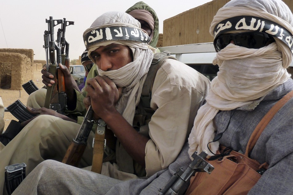 Militiaman from the Ansar Dine Islamic group ride on an armed vehicle in northeastern Mali