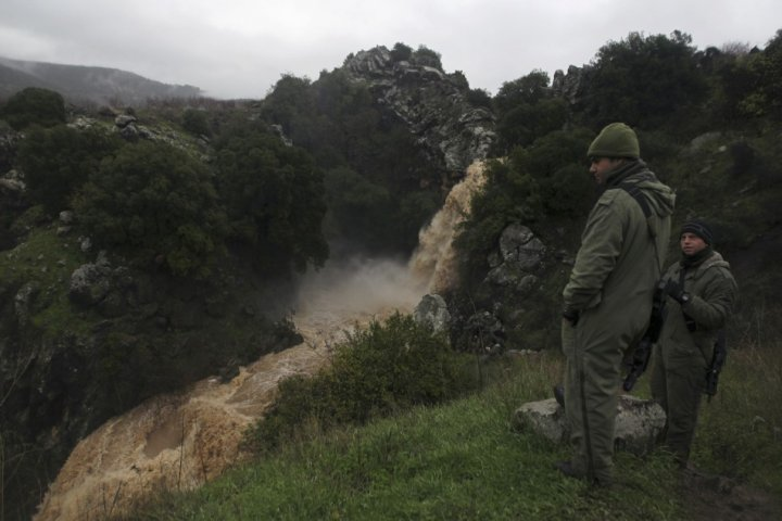 Israeli soldiers look at the Saar waterfall on the slopes of the Golan Heights