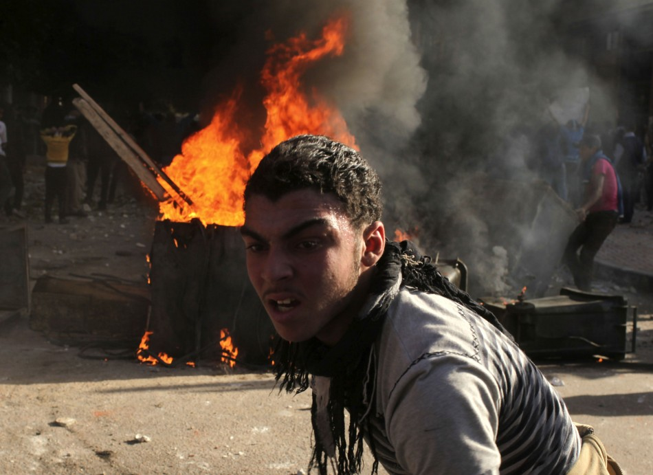 A protester is seen in front of fire set by protesters during clashes against riot police in Alexandria