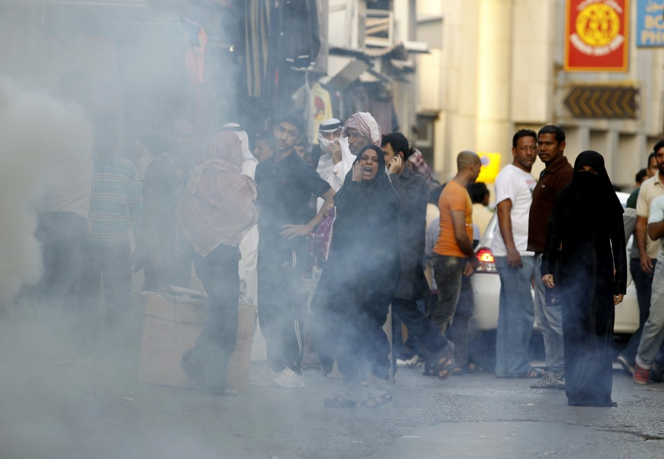 An anti-government protester shouts back at riot police as tear gas smoke is seen during a protest in Manama