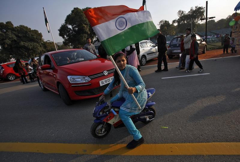 A woman waves Indias national flag as she rides her mini bike near the India Gate during the Republic Day celebrations in New Delhi January 26, 2013.